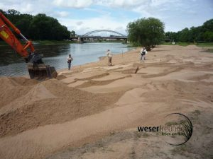 mit Bagger und Schaufeln wird der Sand verteilt